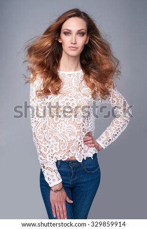 Half length portrait of fashion model in lace top posing over gray background with hair flying on wind - stock photo