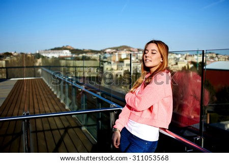 Half length portrait of fashionable gorgeous female dressed in trendy clothes posing for the camera outdoors on sunny summer day,happy young hipster girl enjoying the sun and tranquility while resting - stock photo