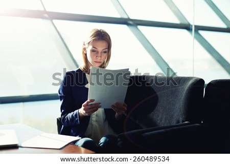Half length portrait of female managing director examining paperwork in bight light office interior, attractive business woman read some documents before meeting, soft focus, filtered image - stock photo
