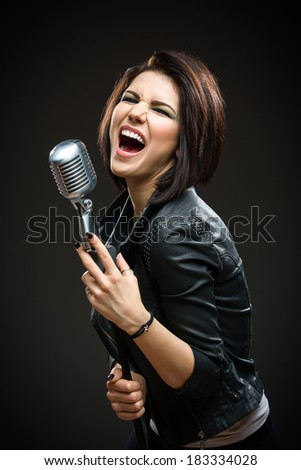 Half-length portrait of female rock musician wearing black jacket and keeping mike on grey background. Concept of music and rave - stock photo