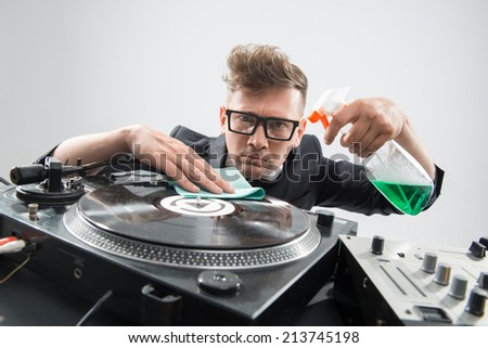 Half-length portrait of funny hipster looking stylish DJ in tuxedo, spectacles and headphones cleaning his turntable isolated on white
