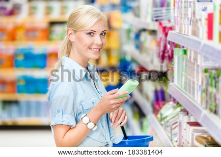 Half length portrait of girl at the shop choosing cosmetics among the great variety of products. Concept of consumerism, retail and purchase - stock photo
