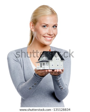 Half-length portrait of girl in grey pullover with small model house, isolated on white - stock photo
