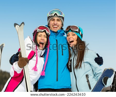 Half-length portrait of group of embracing skier friends. Concept of cute winter sport and funny vacations with friends - stock photo
