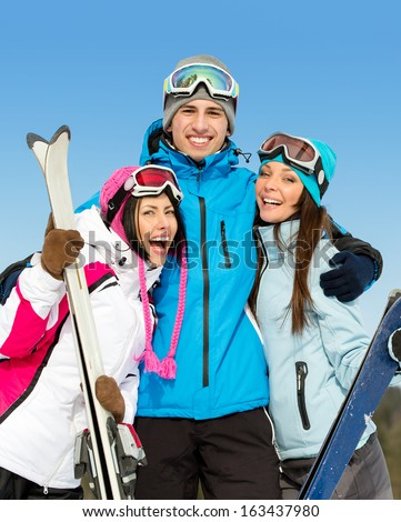 Half-length portrait of group of hugging downhill skier friends. Concept of cute winter sport and funny vacations with friends
