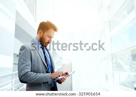 Half length portrait of handsome businessman concentrated watching in touch pad while standing in hallway of his company, young successful intelligent male in suit use digital tablet during work break - stock photo
