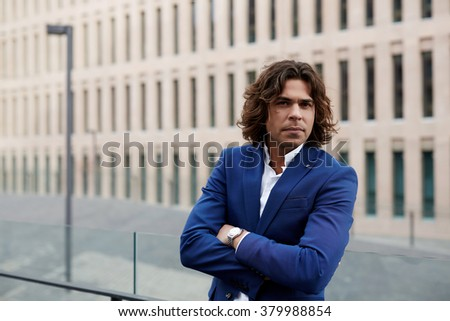 Half length portrait of handsome businessman standing with crossed arms outdoors during work break, successful male entrepreneur dressed in elegant blue suit resting outside after meeting with client - stock photo