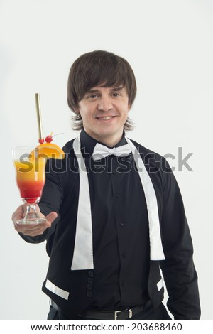 Half-length portrait of handsome dark-haired smiling barman wearing elegant black shirt and white bow-tie suggested us very delicious orange cocktail. Isolated on the white backgound - stock photo