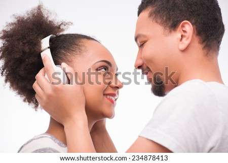 Half-length portrait of handsome man wearing white T-shirt standing aside with closed eyes putting on the earphones on his girlfriend standing opposite him. Isolated on white background