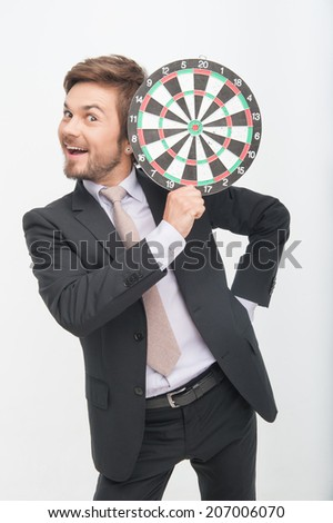 Half-length portrait of handsome smiling young man wearing great black suit holding dartboard near his head and thinking that this game is perfect - stock photo