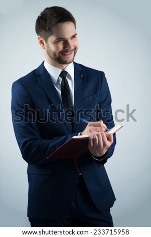 Half-length portrait of handsome young bearded smiling man wearing white shirt tie and blue jacket writing something in his dairy. Isolated on white background - stock photo