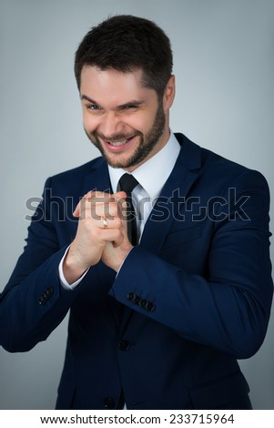 Half-length portrait of handsome young exited man wearing white shirt tie and blue suit crying about his luck. Isolated on white background - stock photo