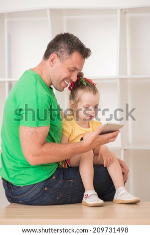 Half-length portrait of happy smiling father and child using electronic tablet at home sitting on desk