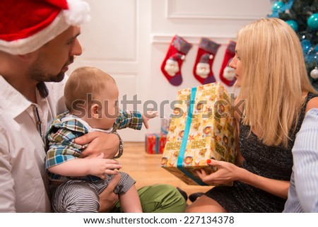 Half-length portrait of happy young family consisted of mom dad and little baby sitting on the floor near the Christmas tree unpacking their present celebrating the New Year holiday - stock photo