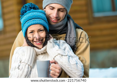 Half-length portrait of hugging couple drinking tea outdoors during winter vacations - stock photo