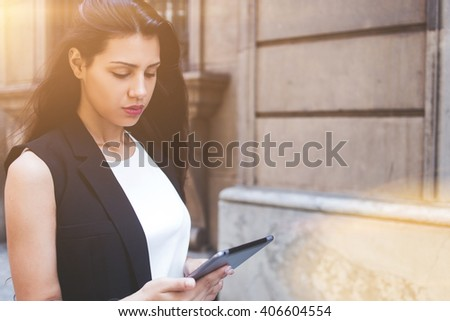 Half length portrait of latin business woman reading fashion news on touch pad while walking on the street, modern female using digital tablet computer for navigation during strolling in urban setting - stock photo