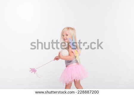 Half-length portrait of little fair-haired lovely smiling girl wearing pretty grey vest pink skirt and white wings going somewhere holding a magic wand looking at us