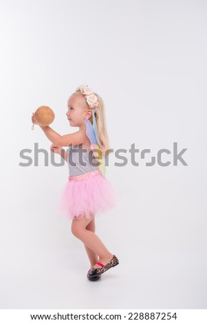 Half-length portrait of little fair-haired lovely smiling girl wearing pretty grey vest pink skirt and white wings playing with balls. Isolated on white background - stock photo