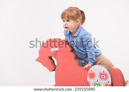 Half-length portrait of little lovely smiling girl wearing blue shirt and brown pants climbing up on the pink wooden toy horse. Isolated on the white background - stock photo