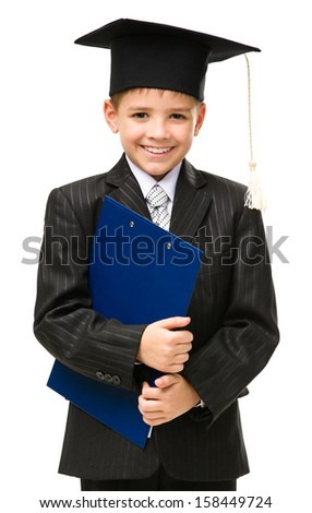 Half-length portrait of little student wearing academic cap and keeping folder, isolated on white. Concept of leadership and success