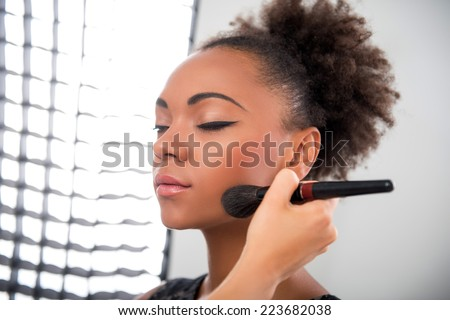 Half-length portrait of lovely African model standing in the studio with closed eyes waiting until her make-up will be ready - stock photo