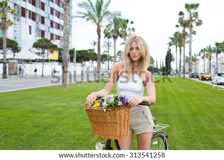 Half length portrait of lovely stylish hipster girl posing in the park with her vintage bicycle with a basket of summer flowers, Sweden female rest after riding through the city during summer holidays - stock photo