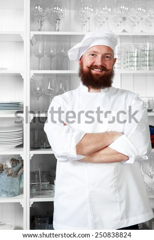 Half length portrait of male chef cook with arms crossed standing in modern luxury kitchen - stock photo