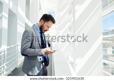 Half length portrait of man managing director dressed in elegant clothes using mobile phone while resting after briefing, young smart male entrepreneur reading something on cell telephone during break - stock photo