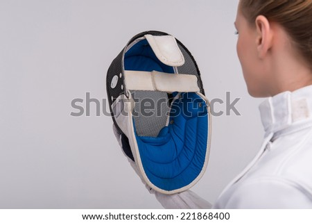Half-length portrait of pretty girl wearing fencing costume looking straight at her blue fencing mask. Isolated on white background - stock photo