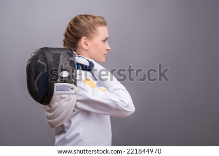 Half-length portrait of pretty serious girl wearing fencing costume standing aside holding her fencing mask on her shoulder. Isolated on dark background - stock photo