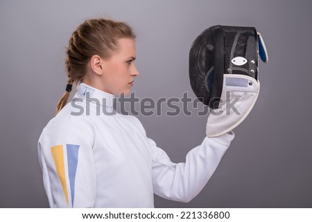Half-length portrait of pretty serious girl wearing fencing costume standing aside looking at her fencing mask. Isolated on dark background - stock photo