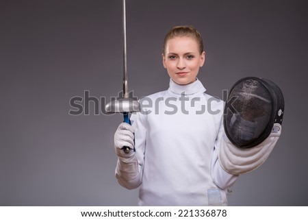 Half-length portrait of pretty smiling girl wearing fencing costume holding the rapier in one hand and fencing mask in another. Isolated on dark background - stock photo