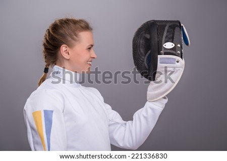 Half-length portrait of pretty smiling girl wearing fencing costume standing aside looking at her fencing mask. Isolated on dark background - stock photo