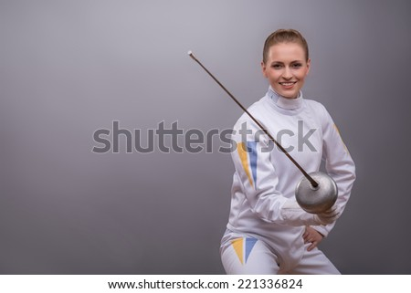 Half-length portrait of pretty smiling girl wearing white fencing costume holding a rapier in her hand waiting for the adversary. Isolated on dark background - stock photo