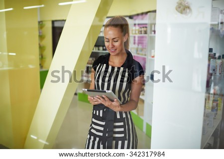 Half length portrait of prosperous smiling female owner reading something on touch pad while standing in cosmetic shop, happy charming woman consultant using touch pad during work day in pharmacy   - stock photo