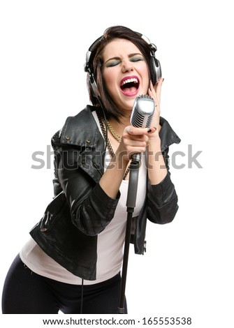 Half-length portrait of rock singer with earphones wearing leather jacket and keeping static microphone, isolated on white. Concept of rock music and rave - stock photo