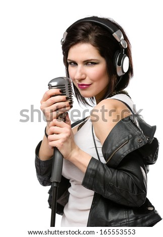 Half-length portrait of rock singer with earphones wearing leather jacket and keeping static mike, isolated on white. Concept of rock music and rave