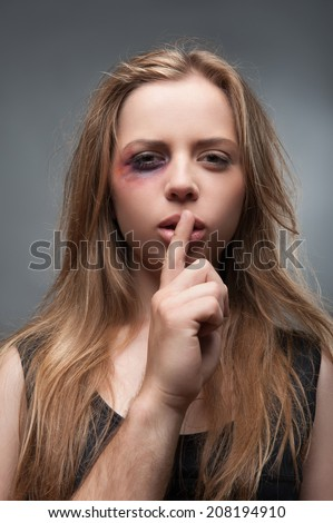Half-length portrait of scared fair-haired young girl with the black eye wanted but cannot tell us the truth. Isolated on grey background - stock photo