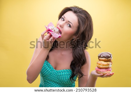 Half-length portrait of sexy dark-haired woman holding in one hand three doughnuts and trying to bite pound cake in another. Isolated on yellow background - stock photo