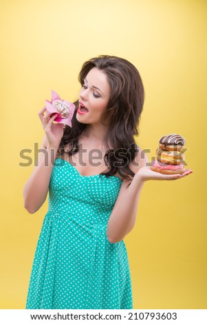 Half-length portrait of sexy dark-haired woman holding in one hand three doughnuts and trying to bite pound cake in another. Isolated on yellow background