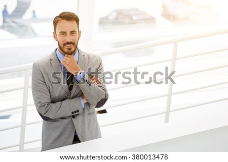 Half length portrait of smiling young skilled businessman standing near copy space in modern office interior, portrait of happy male entrepreneur owner of prosperous company dressed in luxury suit  - stock photo