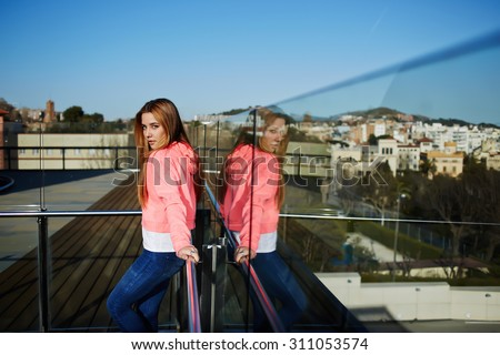 Half length portrait of stylish hipster girl posing for the camera while standing outdoors with beautiful view, attractive female dressed in trendy basic clothes looking to you,cute girl in sweat wear - stock photo
