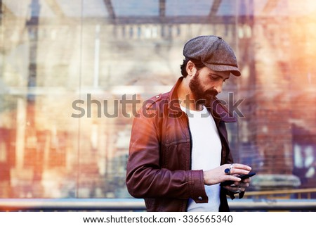 Half length portrait of stylish men chatting on his cell telephone while standing in urban setting, hipster male with dressed in trendy clothes reading message on mobile phone during walk in cool day  - stock photo