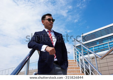 Half length portrait of stylish successful elegant men smoking cigarette in the fresh air during work break in office, confident managing director in formal wear relaxing outdoors in sunny summer day - stock photo