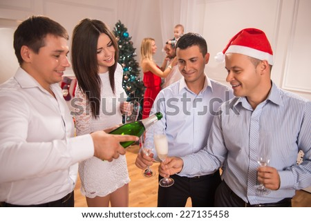 Half-length portrait of the company of happy smartly-dressed friends standing together greeting each other with the New Year holiday drinking Champagne having fun - stock photo