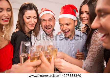 Half-length portrait of the company of happy young smiling friends standing together drinking the champagne greeting each other with the New Year and having fun - stock photo