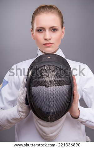 Half-length portrait of the fair-haired sad girl wearing white fencing costume holding the fencing mask in front of her. Isolated on grey background - stock photo