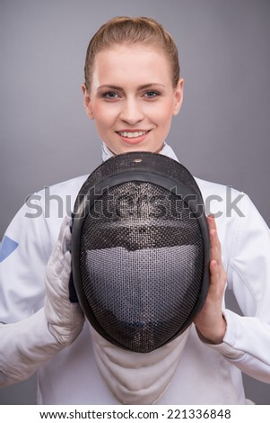 Half-length portrait of the fair-haired smiling girl wearing white fencing costume holding the fencing mask in front of her. Isolated on grey background - stock photo