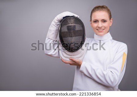 Half-length portrait of the fair-haired smiling girl wearing white fencing costume standing aside showing us her fencing mask. Isolated on grey background - stock photo