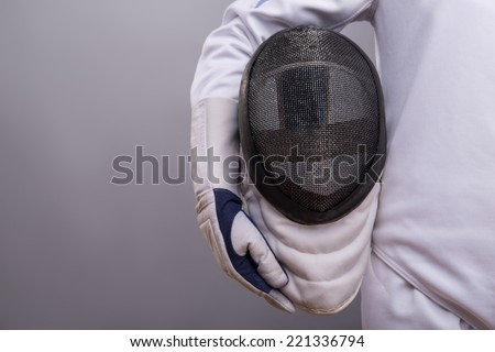 Half-length portrait of the girl wearing white fencing costume holding the fencing mask. Isolated on grey background - stock photo